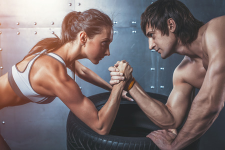 Photo pour Athlete muscular sportsmen man and woman with hands clasped arm wrestling challenge between a young couple Crossfit fitness sport training lifestyle bodybuilding concept - image libre de droit