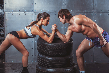 Foto de Athlete muscular sportsmen man and woman with hands clasped arm wrestling challenge between a young couple Crossfit fitness sport training lifestyle bodybuilding concept - Imagen libre de derechos