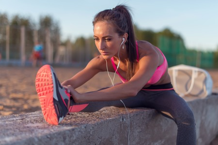 Photo pour Fitness model athlete girl warm up stretching her hamstrings, leg and back. Young woman exercising with headphones listening music outdoors on beach or sports ground at evening summer. - image libre de droit