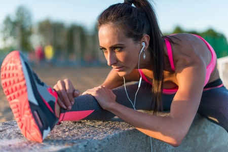 Foto de Athletic woman stretching her hamstring, legs exercise training fitness before workout outside on a beach at summer evening with headphones listening music. - Imagen libre de derechos
