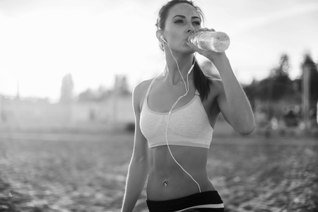 Foto de Beautiful fitness athlete woman resting drinking water after work out exercising on beach summer evening in sunny sunshine outdoor portrait. - Imagen libre de derechos