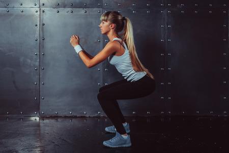 Foto de Athletic young woman fitness model warming up doing squats exercise for the buttocks concept sport slimming healthy lifestyle. - Imagen libre de derechos