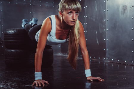 sporty athlete woman doing push ups on tire strength power training concept cross fit fitness workout sport and lifestyle.