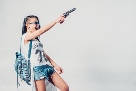 Foto de Fashion swag sexy girl holding gun woman having fun  hooligan, rebel - Imagen libre de derechos
