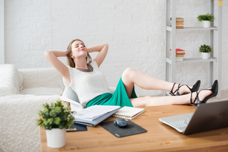 Photo for Businesswoman resting relaxing legs on the table hands behind her head and sitting on a chair in office - Royalty Free Image