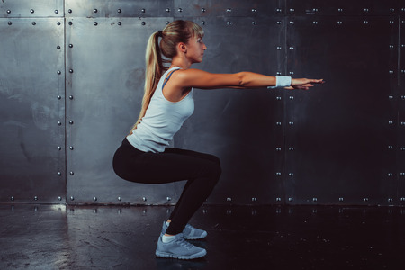 Photo for Athletic young woman fitness model warming up doing squats exercise for the buttocks concept sport slimming healthy lifestyle. - Royalty Free Image