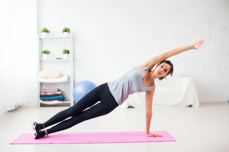 Fit woman doing side plank yoga pose at home in the living room on mat Concept pilates fitness healthy lifestyle