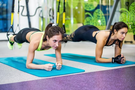 Photo for Fit girls in gym doing plank exercise for back spine and posture Concept pilates fitness sport - Royalty Free Image