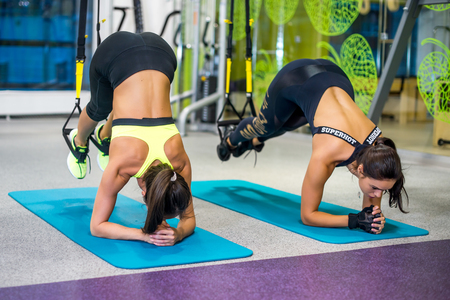 Photo for Woman exercising with suspension straps in fitness club or gym - Royalty Free Image