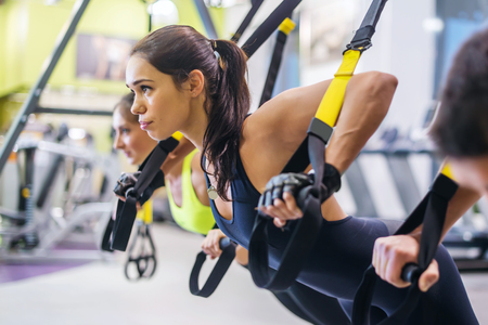 Foto de Women doing push ups training arms with trx fitness straps in the gym Concept workout healthy lifestyle sport - Imagen libre de derechos