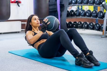 Photo pour Work out fitness woman doing sit ups abs abdominal crunches core exercises with medecine ball - image libre de droit
