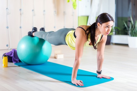 Photo pour Woman doing pilates exercises with fit ball in gym or yoga class - image libre de droit