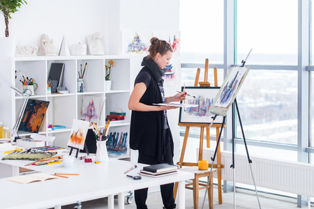 Photo for Female painter drawing in art studio using easel. Portrait of a young woman painting with aquarelle paints on white canvas, side view portrait. - Royalty Free Image