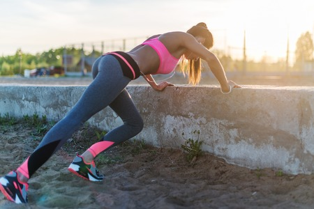 Photo for Fitness woman doing push ups Outdoor training workout summer evening. Concept sport healthy lifestyle - Royalty Free Image