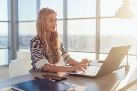 Photo for Young beautiful female copywriter typing texts and blogs in spacious light office, her workplace, using pc keyboard. Busy woman working - Royalty Free Image
