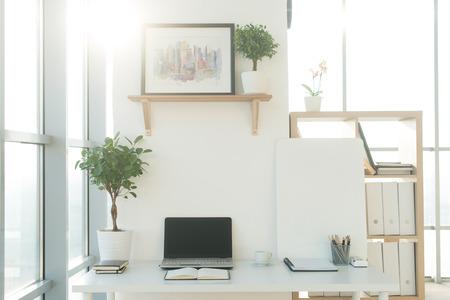 Foto de Side view picture of studio workplace with blank notebook, laptop. Designer comfortable work table, home office - Imagen libre de derechos