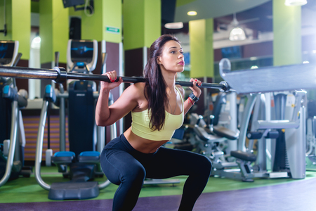 Foto de Fit woman doing squat with barbell in the gym - Imagen libre de derechos