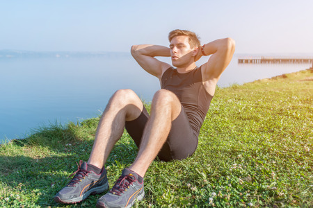 Photo for Sporty young man doing sit-ups abs crunches in nature - Royalty Free Image