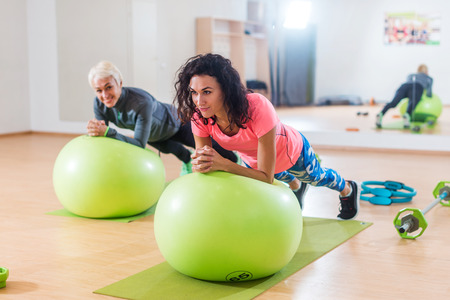 Foto de Two happy sportswomen exercising with a Swiss ball doing plank exercise in gym - Imagen libre de derechos