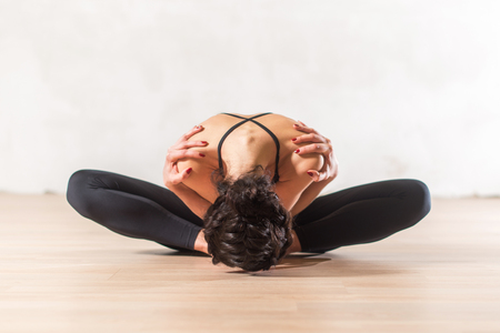 Foto de Dancer doing advanced butterfly stretch exercise sitting leaning forward holding shoulders. Young flexible woman  in beautiful sensual pose. - Imagen libre de derechos