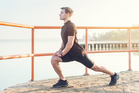 Photo for Fitness man stretching his leg muscles outdoors. - Royalty Free Image