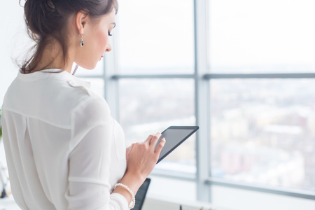 Photo for Close-up side view portrait of an employee texting, sending and reading messages during her break at the workplace. - Royalty Free Image