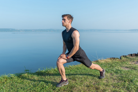 Photo pour Young fit man stretching legs outdoors doing forward lunge. - image libre de droit