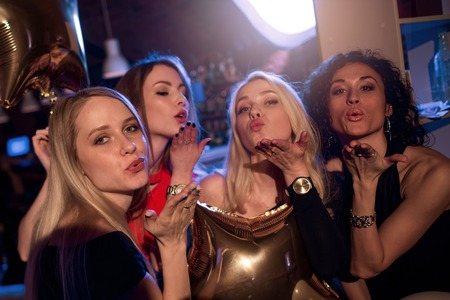 Photo for Group of attractive gorgeous girls blowing kisses looking at camera in nightclub - Royalty Free Image
