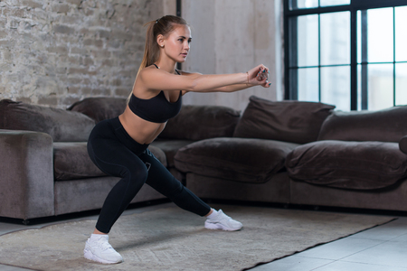 Photo for Beautiful fit girl doing home workout performing lateral lunges in a sitting room - Royalty Free Image