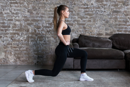 Photo for Profile view of sporty girl doing lunges working-out leg muscles and glutes in loft interior - Royalty Free Image
