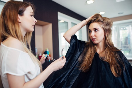 Photo pour Hair stylist working on female customer s hairdo clipping strands with hair pins in hairdressing studio - image libre de droit
