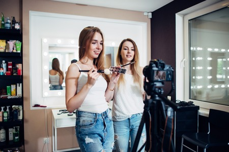 Photo pour Two friends doing a makeup products review shooting a video blog standing in front of camera - image libre de droit