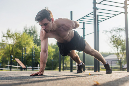 Photo for Athlete young man doing one-arm push-up exercise working out his upper body muscles outside in summer. - Royalty Free Image