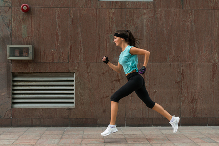 Photo pour Side view of sporty young woman running on a sidewalk. - image libre de droit