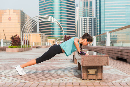Foto de Fitness woman doing feet elevated push-ups on a bench in the city. Sporty girl exercising outdoors - Imagen libre de derechos