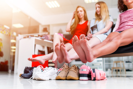 Foto de Young smiling girlfriends sitting in a clothing store looking at their bare feet and pile of new shoes and laughing - Imagen libre de derechos