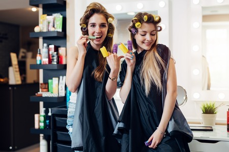 Photo pour Young pretty girls in capes with hair curlers goofing around in beauty salon. Girlfriends showing devil horn and piece gesture with rollers on fingers having fun together - image libre de droit
