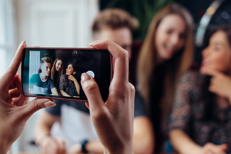 Photo for Female hands taking photo with smartphone of young cheerful friends, blurred background - Royalty Free Image