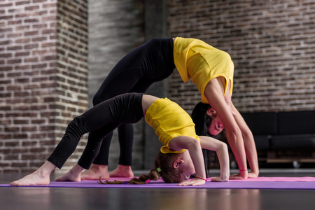Foto de Young sporty mother and little girl doing stretching gymnastic exercises together standing in crab posture on mat in loft studio - Imagen libre de derechos