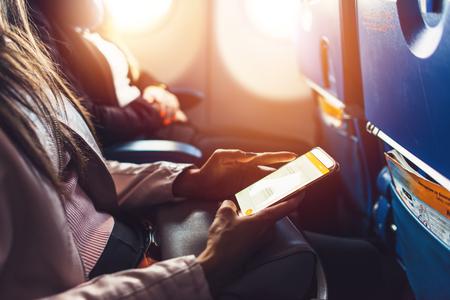 Foto de Close-up image of female hands holding smartphone sitting in the airplane - Imagen libre de derechos