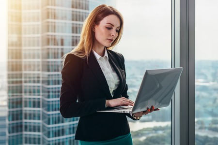 Photo pour Young female lawyer working in her luxurious office holding a laptop standing against panoramic window with a view on business district - image libre de droit
