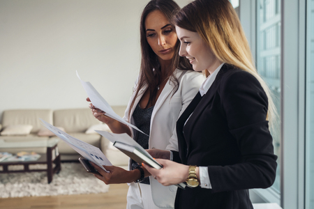 Photo pour Young estate agent showing apartment and discussing the contract and other documents with a customer - image libre de droit
