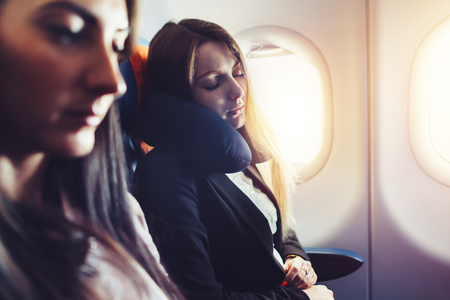 Photo for Two businesswomen sleeping in the airplane using neck cushion while going on business trip - Royalty Free Image