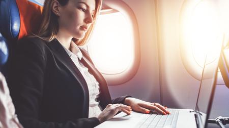 Foto de Woman working using laptop while travelling by plane - Imagen libre de derechos