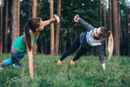 Photo pour Two female buddies doing partner side plank giving high five while training in the forest - image libre de droit