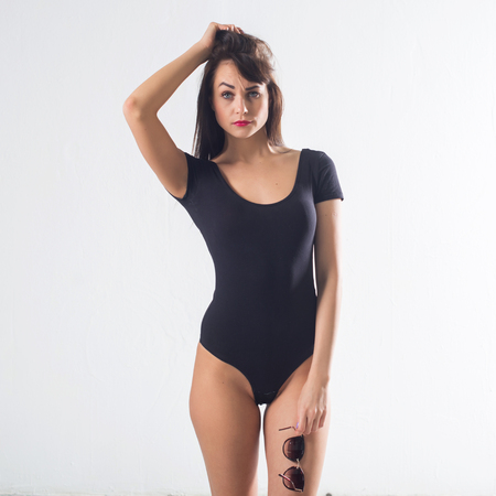 Photo for Cute brunette female model posing, wearing black one piece underwear suit, touching her hair - Royalty Free Image