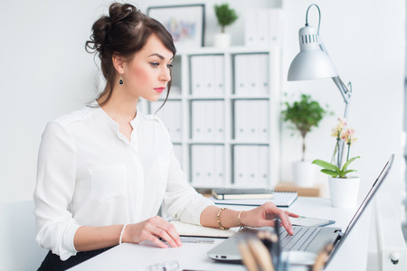 Photo for Attractive businesswoman working at office using pc, searching and studying business ideas on a laptop screen -line. - Royalty Free Image