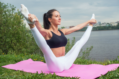Photo pour Woman holding legs apart doing exercises aerobics warming up with gymnastics for flexibility leg stretching workout outdoors. - image libre de droit