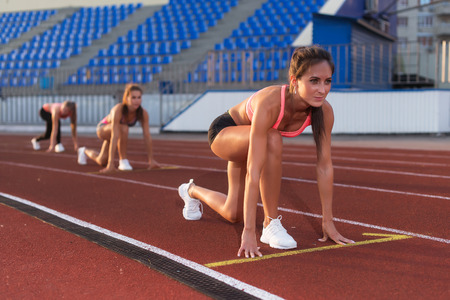 Photo for Women sprinters at starting position ready for race on racetrack. - Royalty Free Image