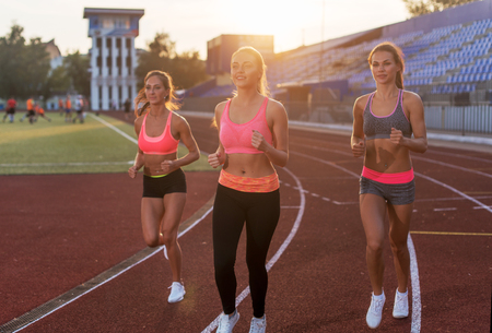 Photo for Group of women athletes running together in stadium. - Royalty Free Image